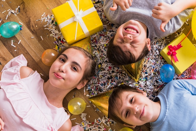 High angle view of friends lying on wooden floor surrounding by gift; balloon and confetti