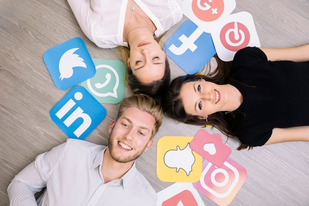 High angle view of friends lying on wooden floor with social media icons