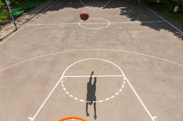 화창한 날 야외 농구 코트에서 그물에 샷을 만드는 젊은 운동 남자 그림자의 백보드에서 높은 각도 보기