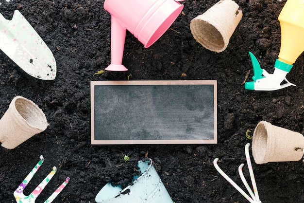 High angle view of gardening tools and blank slate arranging over black dirt
