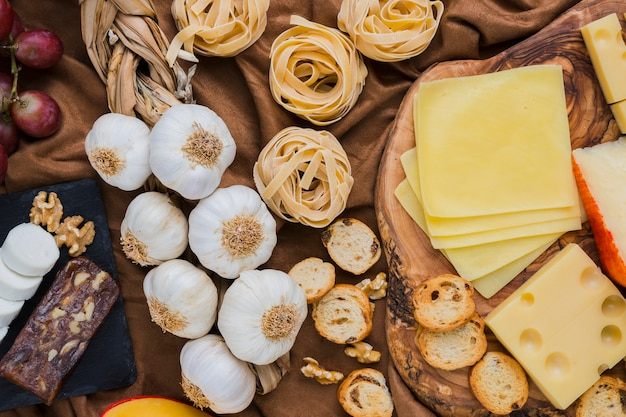 High angle view of garlic bulbs, types of cheese, pasta on brown cloth