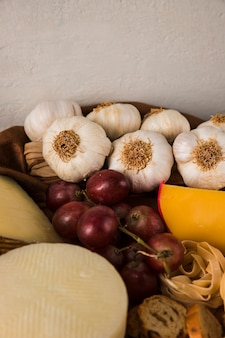 High angle view of garlic; grape; raw pasta and cheese