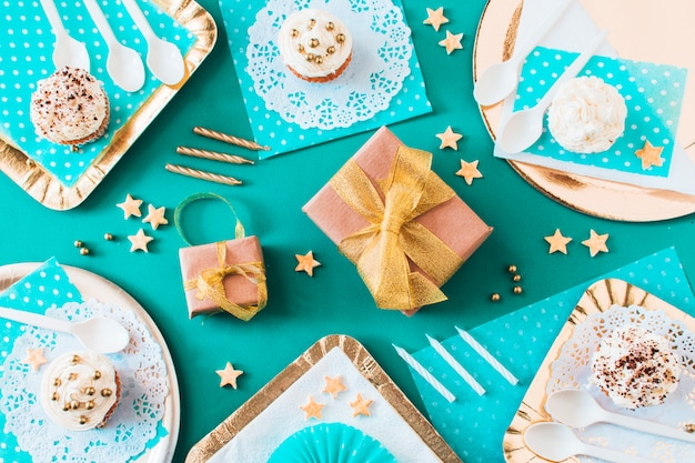 High angle view of gifts with muffins on plate and tray