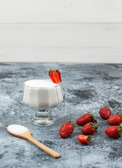 High angle view a glass bowl of yogurt on wicker placemat with wooden spoon and strawberries on dark blue marble and white wooden board background. vertical free space for your text