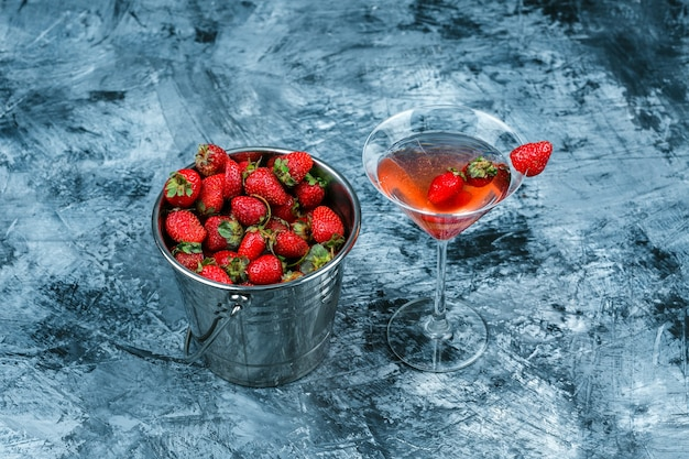 High angle view a glass of strawberry cocktail with a basket of strawberries on dark blue marble surface. horizontal
