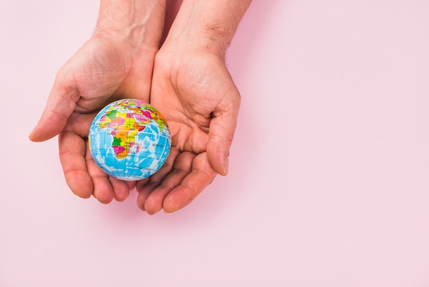 High angle view of a globe on hands against pink surface