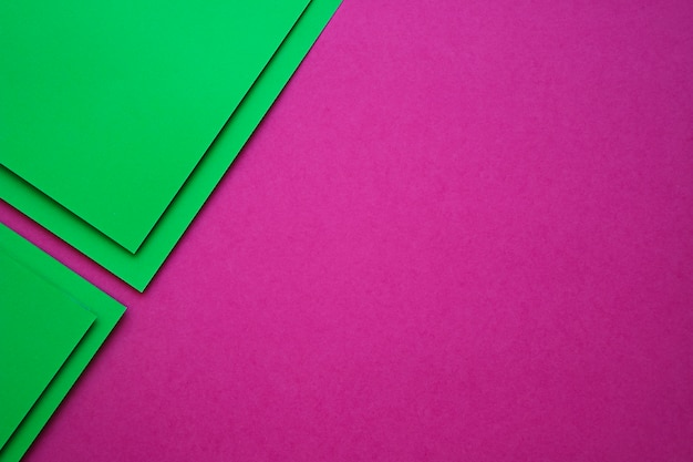 High angle view of green cardboard papers on pink background
