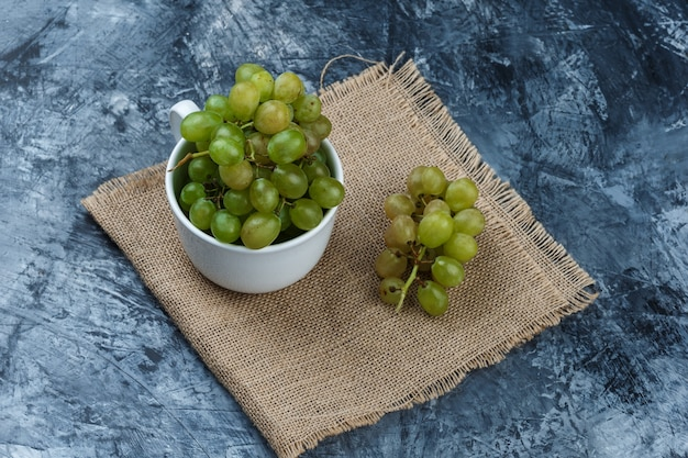 High angle view green grapes in white cup on grunge and piece of sack background. horizontal