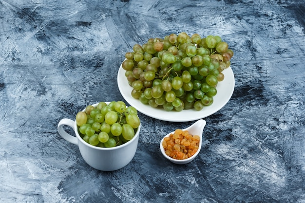 High angle view green grapes in white plate and cup with raisins on grungy plaster background. horizontal