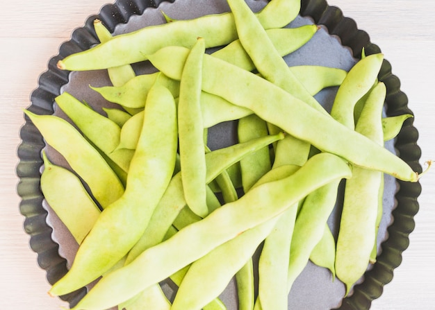 High angle view of green hyacinth beans on baking tray