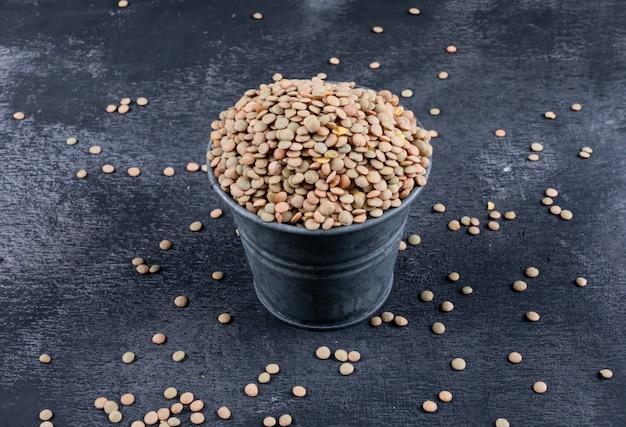 黒い石のテーブルに黒いミニバケツでハイアングルグリーンレンズ豆。横型