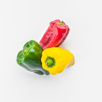High angle view of green; yellow and red bell peppers on white background