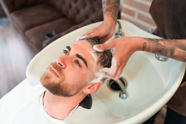 High angle view of a hairdresser with tattoos washing the hair of a young male customer