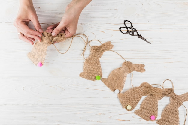 High angle view of hand sewing rabbit shape bunting on wooden textured