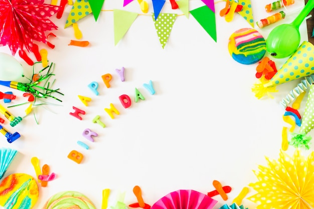 High angle view of happy birthday text with party accessories on white backdrop