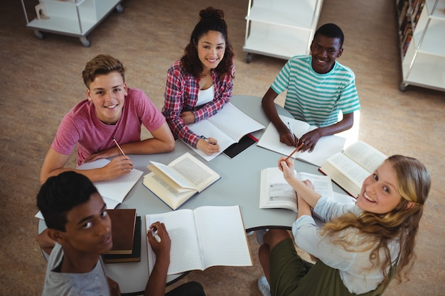High angle view of happy classmates studying in library