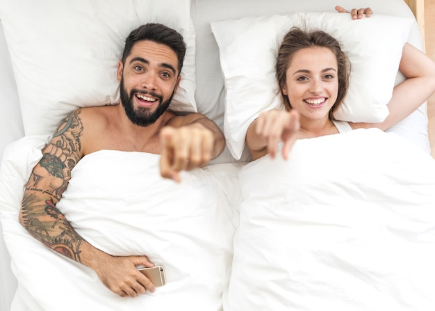 High angle view of happy couple lying on bed pointing fingers