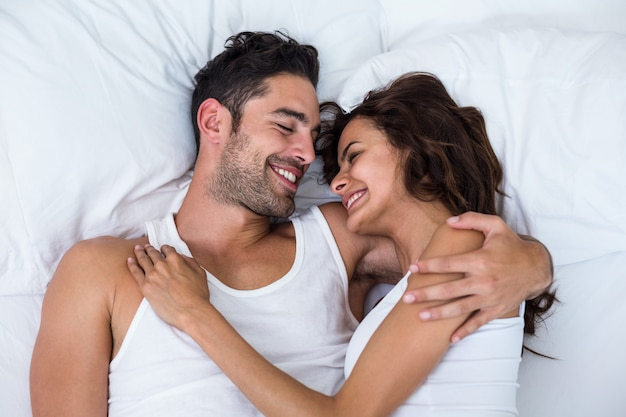 High angle view of happy couple relaxing on bed