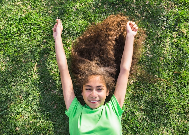 High angle view of a happy girl lying on grass in park
