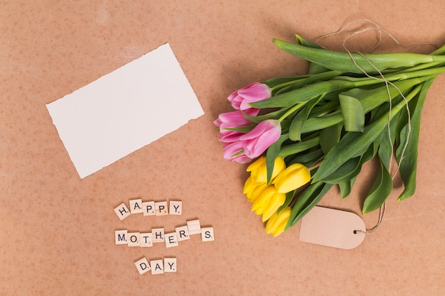 High angle view of happy mother's day text; blank paper and yellow; pink tulip flowers above brown backdrop