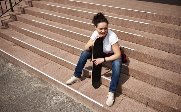 High angle view of a happy smiling mixed race woman with skateboard sitting on steps outdoors