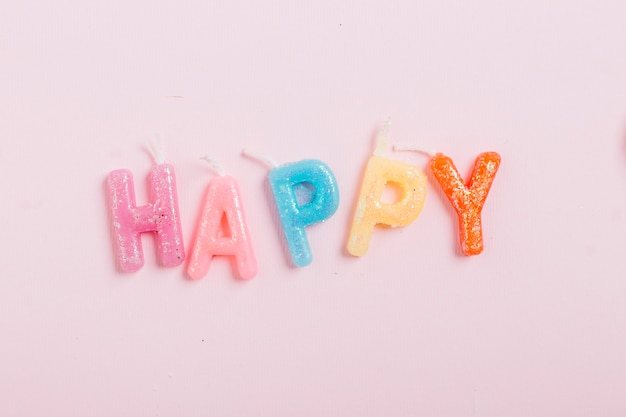 High angle view of happy word candles on pink background