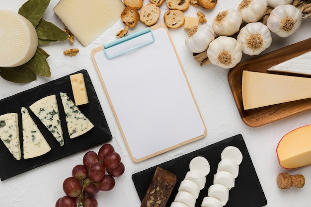 High angle view of healthy ingredient and various cheese with empty clipboard