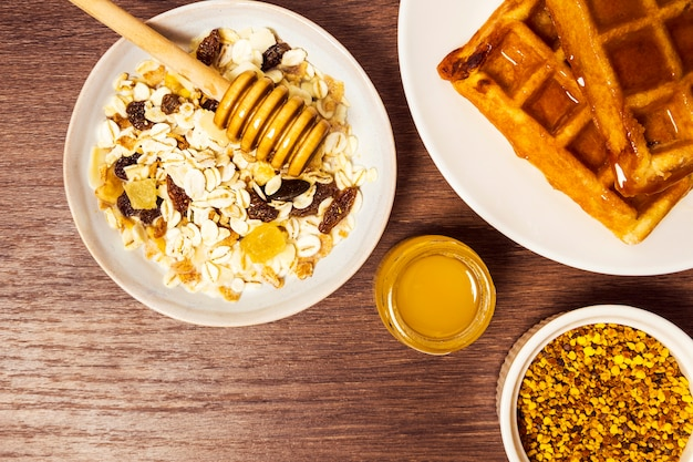 High angle view of healthy oats with waffle and honey