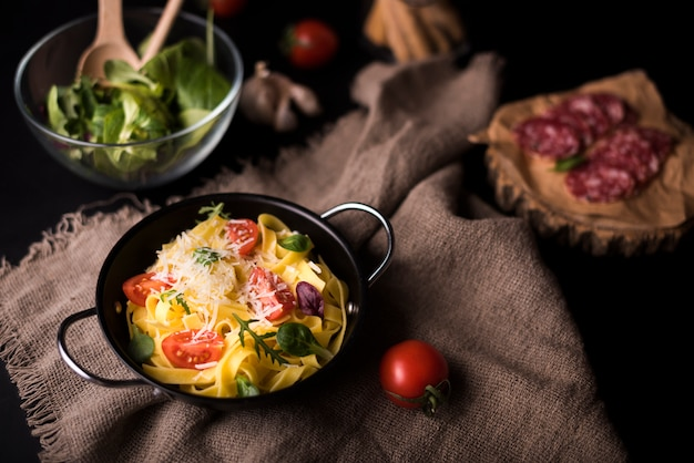 High angle view of healthy pasta in cooking pot on jute textile with cherry tomato and salad