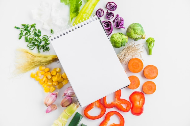 High angle view of healthy raw vegetables and spiral notepad