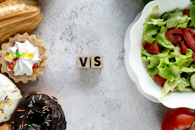 High angle view of healthy vs unhealthy food on concrete background