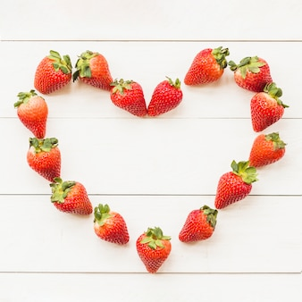 High angle view of heart shape made up of juicy strawberries
