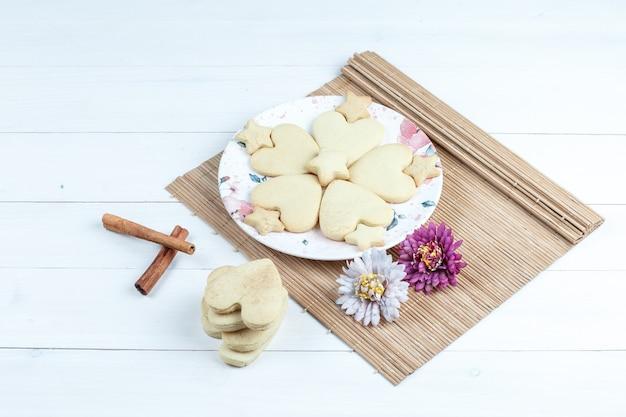 Печенье в форме сердца и звезды под высоким углом, цветы в салфетке с корицей