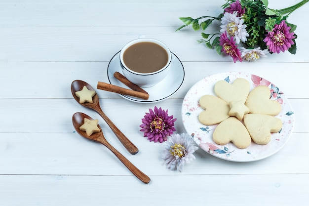 花と白いプレートのハート型と星のクッキーの高角度ビュー
