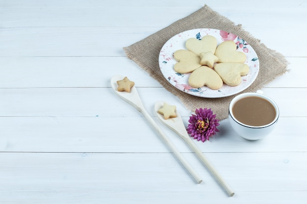 High angle view heart shaped cookies, cup of coffee with flower, star cookies in wooden spoons on white wooden board background. horizontal