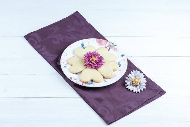 Biscotti a forma di cuore di vista di alto angolo, fiori sulla tovaglietta sul fondo del bordo di legno bianco. orizzontale