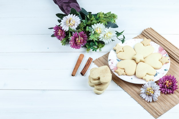 High angle view heart shaped and star cookies, flowers in placemat with cinnamon
