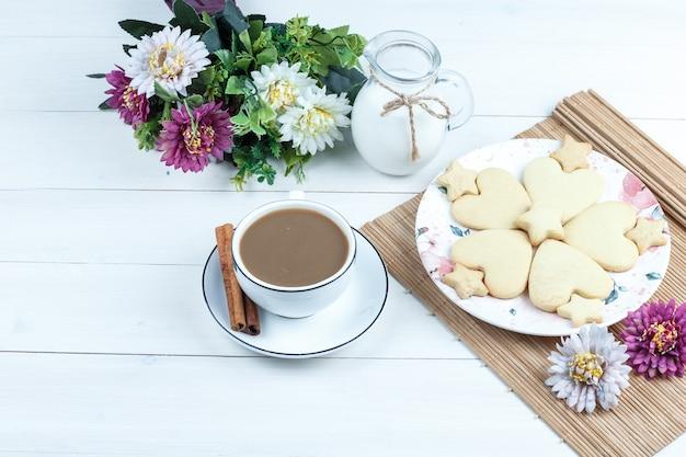 Biscotti a forma di cuore e stella di alta vista, fiori in tovaglietta con brocca di latte