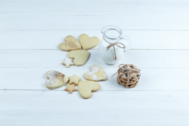 High angle view heart shaped and star cookies with jug of milk on white wooden board background. horizontal