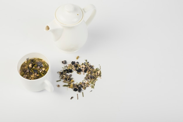 High angle view of herbal tea with teapot on white background