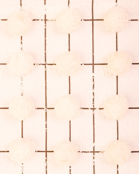 High angle view of homemade coconut chocolate arranged on a row over white checkered table cloth