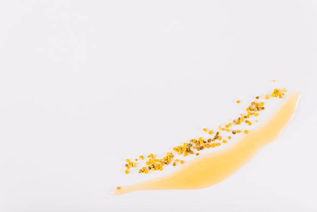 High angle view of honey and bee pollen on white backdrop