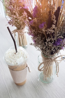 High angle view of iced coffee and whipping cream, decoration with dried flowers