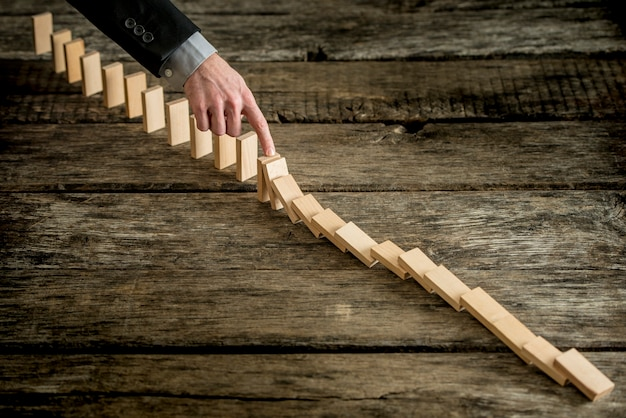 Изображение высокого угла зрения бизнесмена, останавливающего эффект домино над старой грубой деревянной поверхностью стола, концептуальные решения бизнес-проблем.