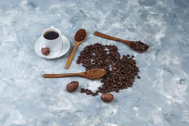 High angle view instant coffee, coffee flour, coffee beans in wooden spoons with cup of coffee, cookies on light blue marble background. horizontal