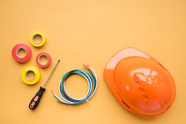 High angle view of insulating tape; screwdriver; wire and orange hard hat over yellow backdrop