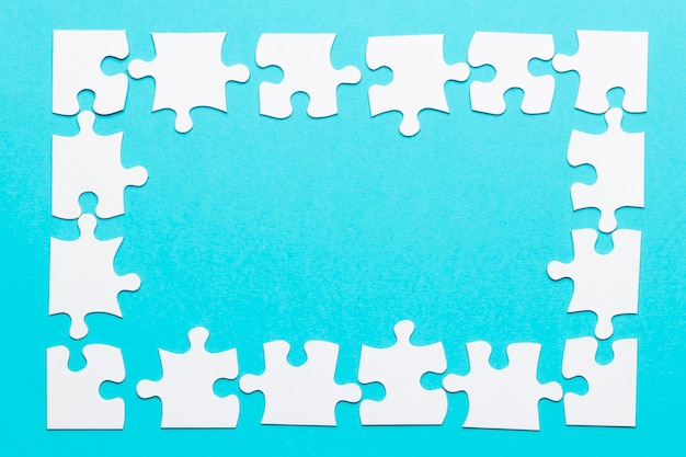 High angle view of jigsaw puzzle frame on blue backdrop
