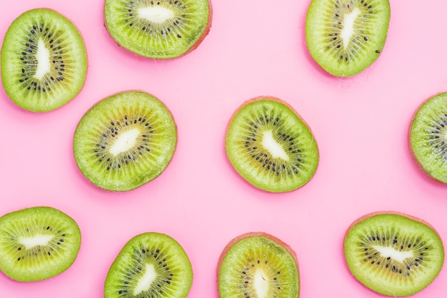 High angle view of kiwi fruit slices on pink background