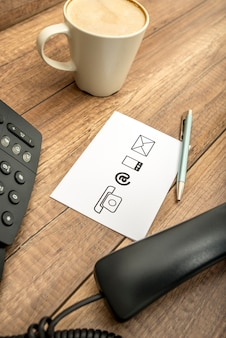 High angle view of landline telephone, receiver, mug of coffee, silver pen and notepad with various  illustrated communication icons on rustic wooden table.