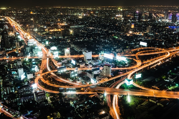 High angle view landscape night scene of cityscape see the bright light bulb of the highway, skyscraper, road, and horizon, residential building of bangkok the capital city of thailand in asia